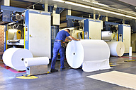 Man moving paper roll in a printing shop - LYF000470
