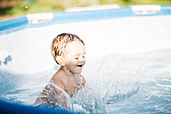 Little boy splashing in a paddling pool - JRFF000044