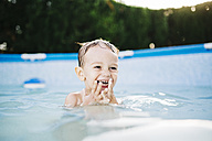 Portrait of happy little boy in a paddling pool - JRFF000053
