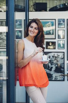 Smiling woman outdoors holding cup of coffee - CHA001429