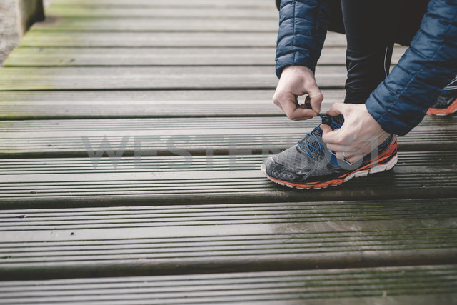 Jogger tying his sneakers on a wooden floor - RAEF000440