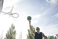 Man spinning a basketball on his finger - ABZF000108