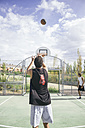 Young man throwing basketball - ABZF000111