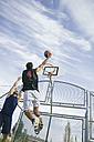 Young man playing basketball, dunking ball - ABZF000115