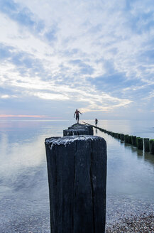 Netherlands, Domburg, men walking on breakwaters at sunset - THA001426