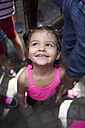 Portrait of smiling little girl standing between adults looking up - ERL000021