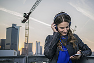 Germany, Frankfurt, smiling woman hearing music with headphones looking at her smartphone - RIBF000253