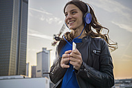 Germany, Frankfurt, smiling woman hearing music with headphones dancing - RIBF000255