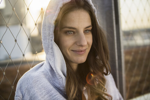 Germany, Frankfurt, portrait of smiling young woman wearing hooded jacket - RIBF000259