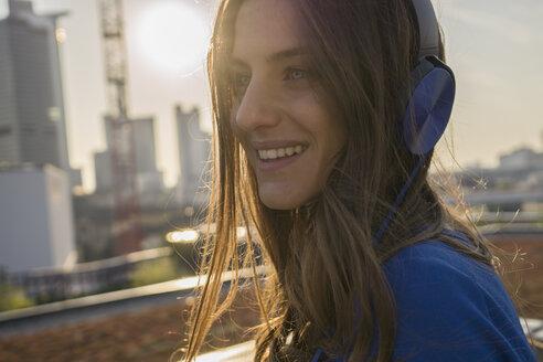 Germany, Frankfurt, portrait of smiling woman hearing music with headphones - RIBF000260
