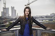 Germany, Frankfurt, portrait of young woman standing on roof terrace - RIBF000307