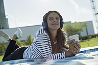 Young woman with coffee to go lying on blanket on a meadow hearing music with headphones - RIBF000267