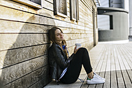 Smiling woman with coffee to go sitting on ground leaning against wooden wall - RIBF000269