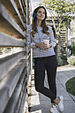Portrait of smiling woman with coffee to go hearing music with headphones - RIBF000271