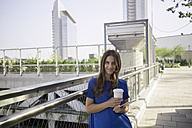 Germany, Frankfurt, portrait of smiling woman with coffee to go and mini tablet - RIBF000276