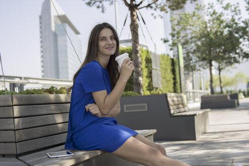 Germany, Frankfurt, businesswoman sitting on a bench with coffee to go - RIBF000278