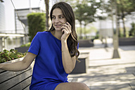 Smiling businesswoman sitting on a bench telephoning with smartphone - RIBF000281