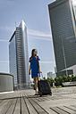 Germany, Frankfurt, businesswoman with smartphone and wheeled luggage standing on roof terrace - RIBF000300