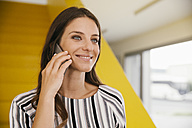 Portrait of smiling young woman telephoning with smartphone in front of yellow stairs - MFF002104