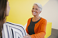 Portrait of smiling mature woman greeting another woman in an office - MFF002110