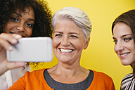 Three women taking a selfie with smartphone in front of a yellow wall - MFF002116