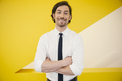 Portrait of mature man wearing shirt and tie standing in front of a yellow wall - MFF002119