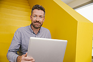 Portrait of smiling mature man with laptop sitting on yellow stairs - MFF002122