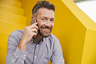 Portrait of smiling mature man telephoning with smartphone sitting on yellow stairs - MFF002125