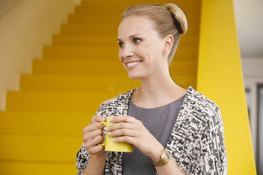 Portrait of smiling young woman with a hot beverage in front of yellow stairs - MFF002130