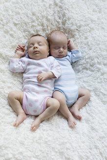 Portrait of newborn twins sleeping side by side - SHKF000360