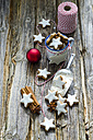 Home-baked cinnamon stars, shovel of flour, spices and red Christmas bauble - ODF001281