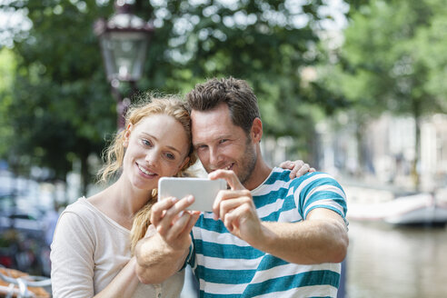 Netherlands, Amsterdam, smiling couple taking a selfie at town canal - FMKF002094