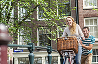 Netherlands, Amsterdam, happy couple with bicycle in the city - FMKF002213