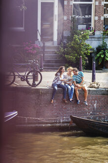 Netherlands, Amsterdam, three friends sitting with digital tablet at town canal - FMKF002110
