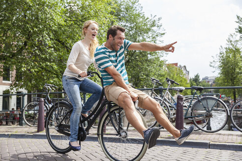 Netherlands, Amsterdam, happy couple riding bicycle in the city - FMKF002112