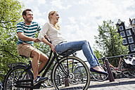 Netherlands, Amsterdam, happy couple riding bicycle in the city - FMKF002091