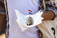 Woman holding napking with matjes herring and Dutch flag - FMKF002118
