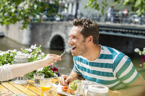 Netherlands, Amsterdam, woman feeding man at outdoor restaurant at town canal - FMKF002126