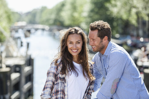 Netherlands, Amsterdam, happy couple at town canal - FMKF002132