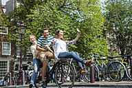 Netherlands, Amsterdam, three playful friends riding on one bicycle in the city - FMKF002146