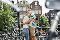 Netherlands, Amsterdam, couple embracing in the city - FMKF002149