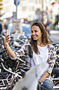 Netherlands, Amsterdam, smiling young woman taking a selfie - FMKF002158