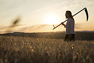 Organic farmer with scythe in barley field at sunrise - MIDF000601