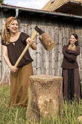 Smiling woman chopping wood - MIDF000614