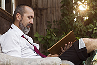 Businessman reading book in the country - MIDF000617