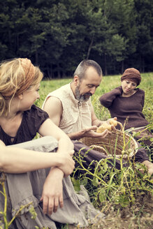 Three people sitting on field with potatoes in wicker basket - MIDF000627