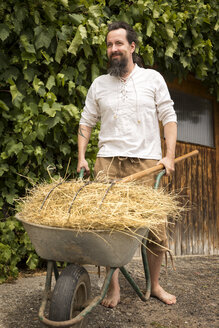 Farmer pushing wheelbarrow with hay - MIDF000636