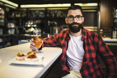 Portrait of hipster with glass of beer and tapas sitting at counter in a pub - JASF000109