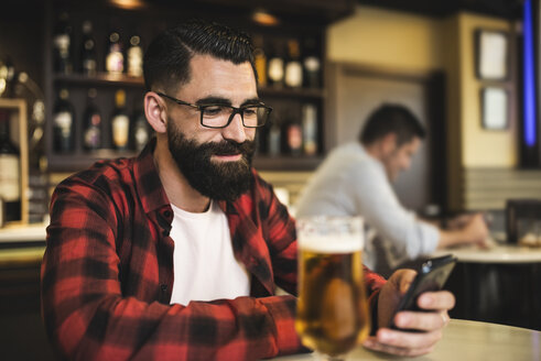 Portrait of hipster with glass of beer looking at his smartphone in a pub - JASF000111
