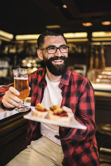 Portrait of happy hipster with glass of beer and tapas sitting at counter in a pub - JASF000112